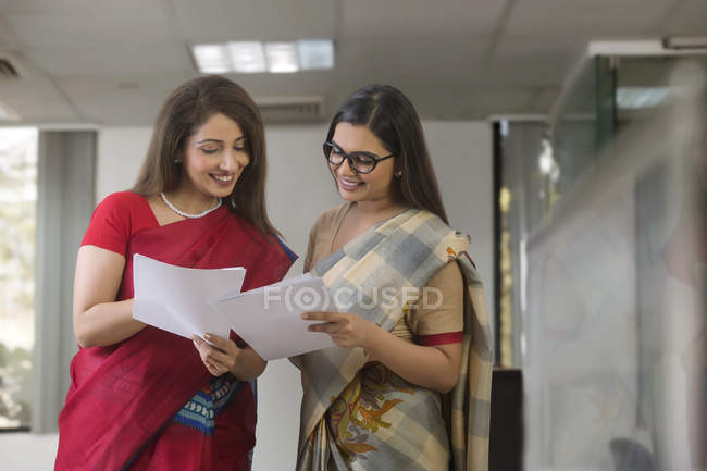 Two businesswomen standing with reports in hand — Stock Photo