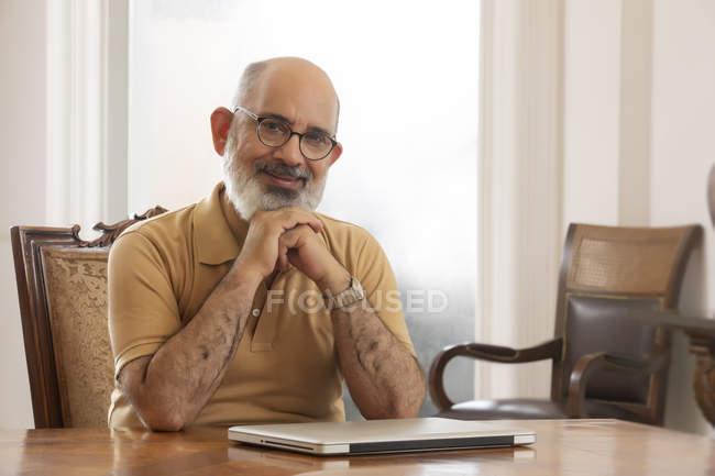 Un vieil homme souriant assis à la table. (Senior) — Photo de stock