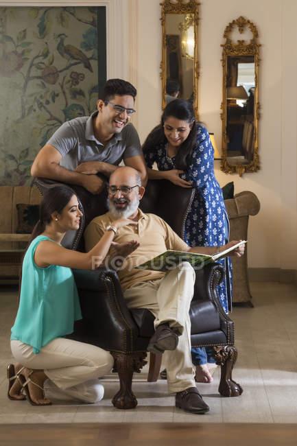 Eine Familie schweißt zusammen, während sie im Wohnzimmer ein Fotoalbum betrachtet. — Stockfoto