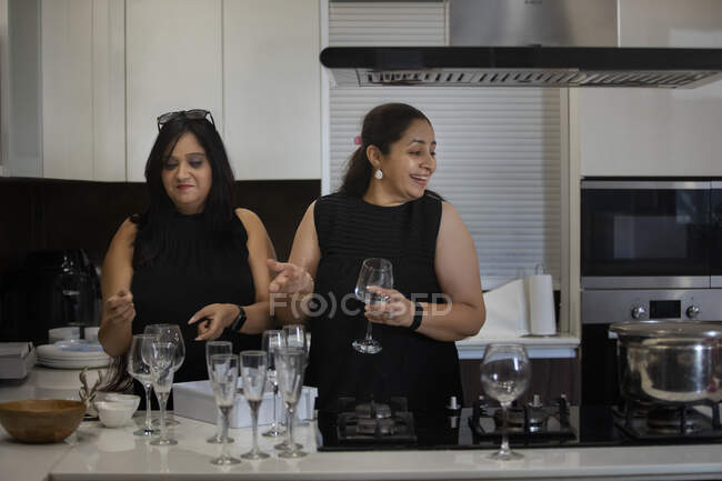 Friends sharing a light moment while pouring drinks at a party. — Stock Photo