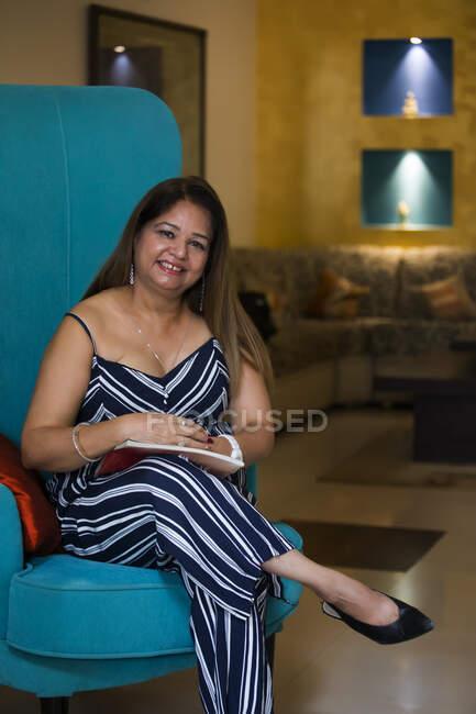Femme assise sur une chaise haute avec un magazine. — Photo de stock