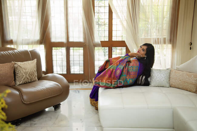 Woman sitting comfortably in her home wearing an Indian suit. — Stock Photo
