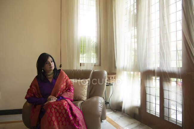 Una donna ben vestita seduta comodamente su un divano a casa sua . — Foto stock
