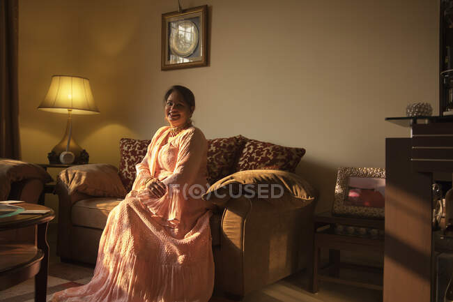 A well dressed woman sitting comfortably at her home. — Stock Photo