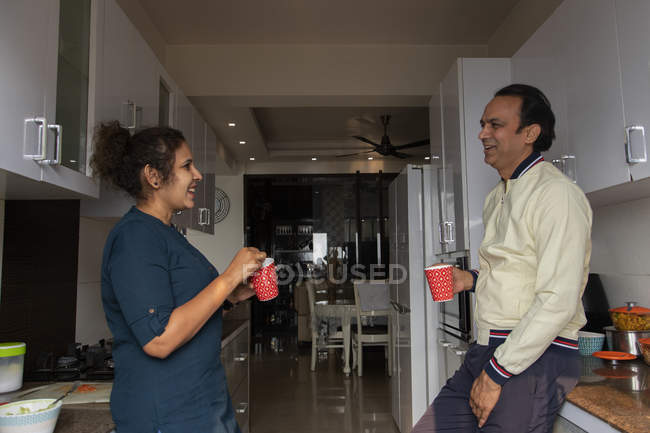 Husband and wife drinking coffee in the kitchen together at home. - foto de stock