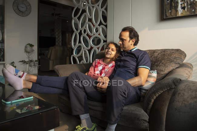 Дівчинка сидить на дивані зі своїм батьком вдома.. — стокове фото