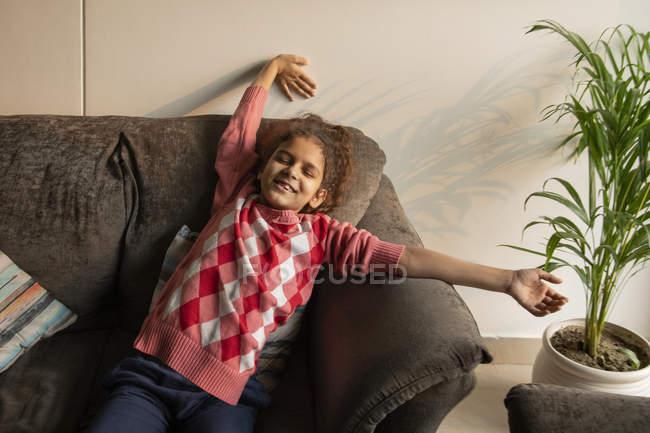 Jeune fille étirant sa fatigue sur le canapé à la maison . — Photo de stock
