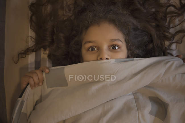 Giovane ragazza guardando fuori sorprendentemente da sotto la coperta. — Foto stock