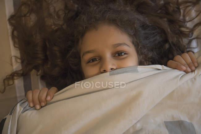 Junges Mädchen lächelt unter der Decke. — Stockfoto