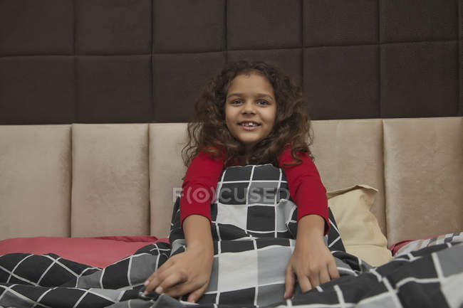 Young girl enjoying the comfort of a blanket at home. — Stock Photo