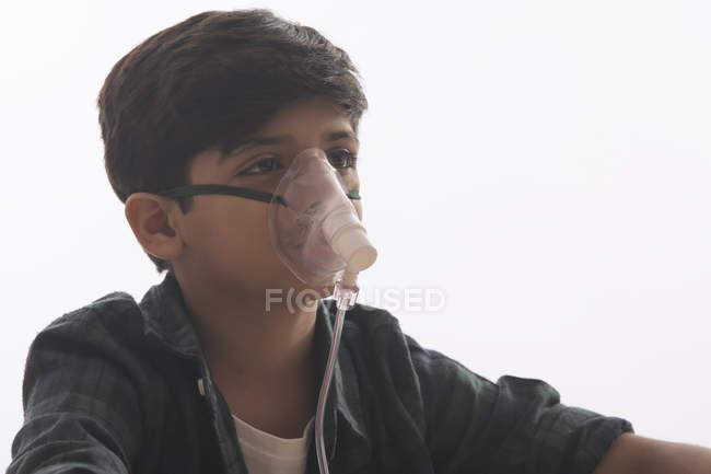 Мальчик с астмой делает ингаляции с маской на лице.( — стоковое фото