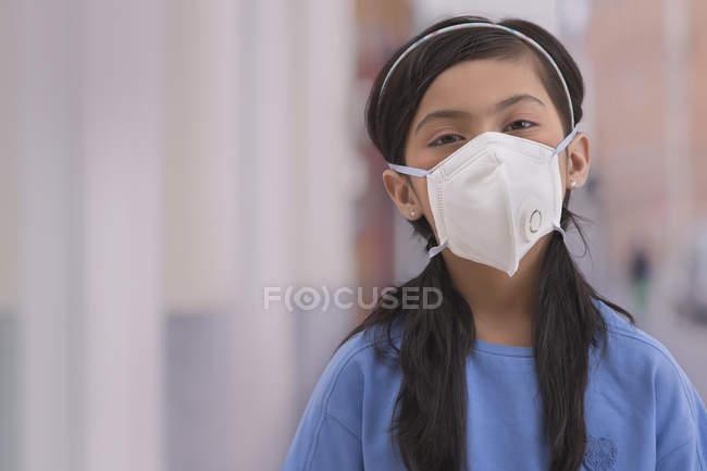 Jovem de pé fora vestindo uma máscara de poluição. — Fotografia de Stock