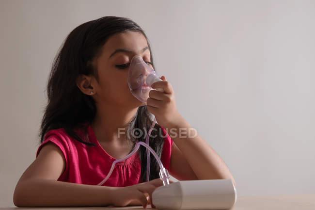 Menina sentada e inalando através de um nebulizador em casa . — Fotografia de Stock