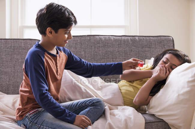 Hermano dando medicina a su hermana enferma mientras ella evita tomarla . - foto de stock