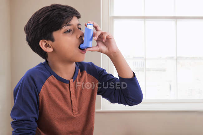 Young asthma patient taking an inhaler. — Stock Photo