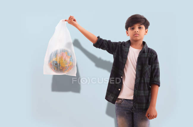 Young boy sending a message about the environment while holding a globe inside a plastic bag. — Stock Photo