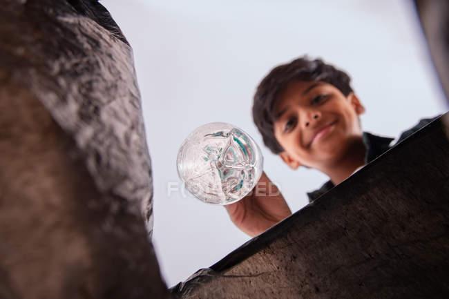 Joven niño lanzando botella de plástico en una bolsa de basura . - foto de stock