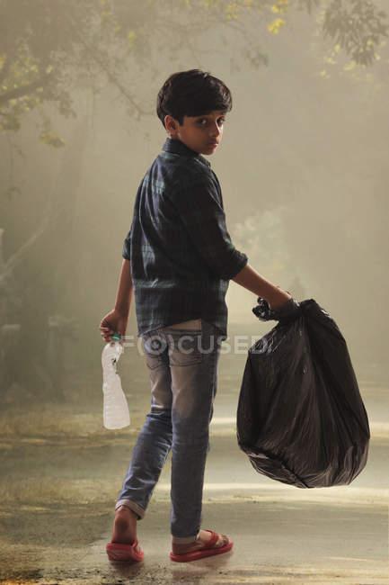 Menino recolhendo lixo das ruas e ajudando o meio ambiente . — Fotografia de Stock