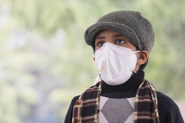 Jovem usando uma máscara de poluição e roupas de inverno . — Fotografia de Stock