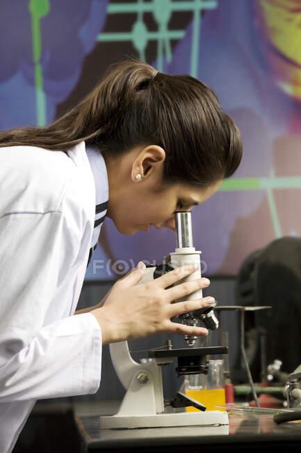 Девочка-подросток смотрит на слайд с микроскопом — стоковое фото