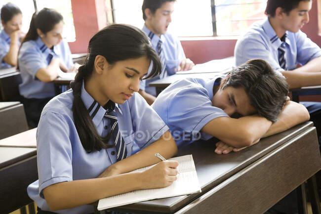 Mädchen schreibt in einem Notizbuch in einem Klassenzimmer — Stockfoto