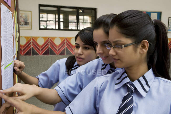 Gli studenti che guardano i risultati degli esami su una bacheca — Foto stock