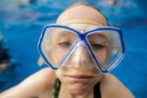 A girl in swimming pool wearing goggles and making a funny face. — Stock Photo