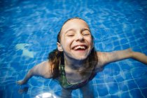 A girl is having fun in a swimming pool during vacation. — Stock Photo