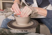 Close up of a woman's hand shaping pottery clay on a pottery wheel in a ceramic workshop. — Stock Photo