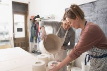 Two ceramic artists are slipcasting ceramics in a pottery workshop. — Stock Photo