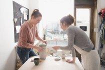 Dos artistas cerámicos están dando los toques finales a una jarra de cerámica en un taller de cerámica . - foto de stock