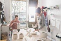 Две керамические художники работают над их керамика в гончарной мастерской — стоковое фото