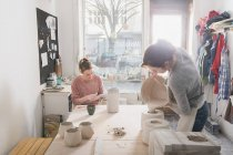 Two ceramic artists are working on their ceramics in a pottery workshop. — Stock Photo