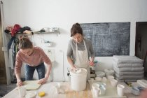 Two ceramic artists are glazing ceramics in a pottery workshop. — Stock Photo