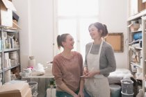 Two smiling ceramic artists portrayed in their pottery workshop. — Stock Photo