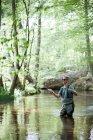 Больной человек в Куликов является летать рыбалка на реке в лесной зоне. — стоковое фото
