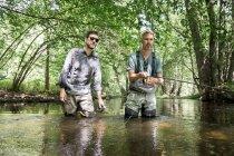 Dos hombres en vadeadores son la pesca con mosca en el río en la zona forestal . - foto de stock