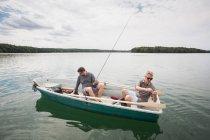 Два кавказьких чоловіків готуєте їх обладнання для нахлистом від човен на озері. — стокове фото