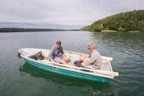 Два кавказьких чоловіків на човні по дорозі літати риболовля на річці. — стокове фото