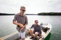 Un uomo sta remando una barca a remi mentre il suo amico è pesca a mosca da una barca sul lago . — Foto stock