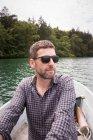 Мужчина гребёт на лодке по озеру . — стоковое фото
