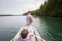 Un homme est aviron une barque tandis que son ami est la pêche à la mouche depuis un bateau sur le lac. — Photo de stock