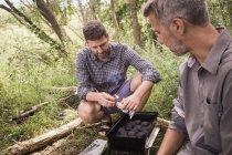Dos hombres están preparando la parrilla para barbacoa en naturaleza abierta. - foto de stock