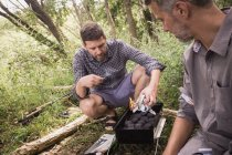 Two men are preparing the grill for a barbeque in open nature. — Stock Photo