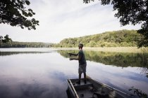 Visão traseira do homem é pesca com mosca de barco no lago . — Fotografia de Stock
