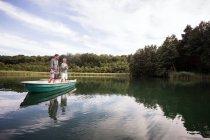 Кавказьких чоловіків є нахлистом в човен на озері. — стокове фото