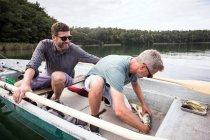 Две Лети рыбаки имеют catched щука с лодки на озере.. — стоковое фото