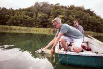 Vista laterale di due pescatori di mosche stanno liberando un luccio in acqua dolce dopo averlo catturato — Foto stock