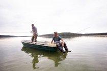 Двое мужчин в сапоги являются fly рыбалка с лодки в озеро — стоковое фото
