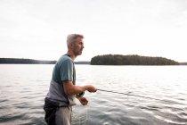Vue latérale de l'homme en cuissardes est la pêche à la mouche depuis un bateau sur le lac. — Photo de stock